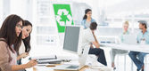 Artists working at desks with recycling sign in background at of — Stock Photo