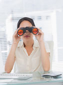 Businesswoman looking through binoculars at desk — Stock Photo
