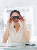 Businesswoman looking through binoculars at desk — Stock Photo