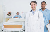 Two smiling doctors with patient in hospital — Stock Photo