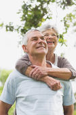 Senior woman embracing man from behind — Stock Photo