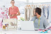 Man using laptop with fashion designer working at studio — Stock Photo