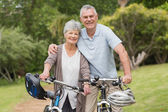 Senior couple on cycle ride at the park — Stock Photo