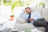 Well dressed man watching tv in the living room — Stock Photo
