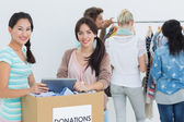 People with clothes donation while using digital tablet — Stock Photo