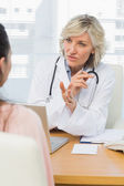 Female doctor listening to patient with concentration — Stock Photo
