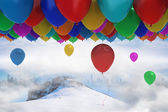Many colourful balloons above snow — Stok fotoğraf