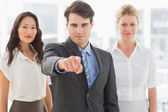 Happy businessman pointing to camera in front of his team — Stock Photo