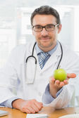 Portrait of a smiling male doctor holding an apple — Stock Photo