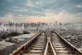 Railway tracks leading to big city — Stockfoto