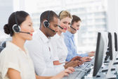 Business colleagues with headsets using computers at desk — Stock Photo