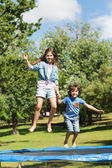 Happy boy and girl jumping high on trampoline in park — Stok fotoğraf