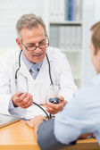 Smiling doctor taking his patients blood pressure — Stock Photo