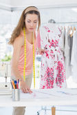 Female fashion designer working on floral dress — Stock Photo