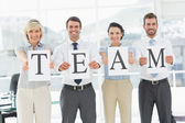 Happy business team holding papers indicating 'team' — Stock Photo