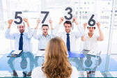 Group of panel judges holding score signs in front of a woman — Stock Photo