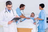 Doctor writing reports with patient and surgeons in background — Stock Photo