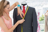 Female fashion designer measuring suit on dummy — Stock Photo