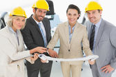 Confident architects with hard hats and blueprint — Stock Photo