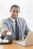Well dressed man handing business card in front of laptop at off — Stock Photo