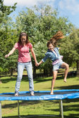 Happy girl and mother jumping high on trampoline in park — Zdjęcie stockowe