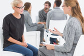 Group therapy session with therapist and client in foreground — Stock Photo