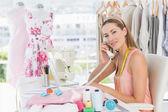 Female fashion designer using phone in studio — Stock Photo