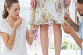 Two fashion designers adjusting dress on model — Stock Photo