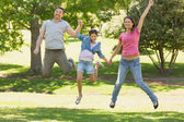 Family of three holding hands and jumping at park — Stock Photo