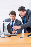 Businessmen using computer at office desk — Stockfoto
