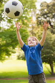 Smiling young boy playing with ball in park — Stock Photo