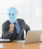 Businessman with sad smiley faced balloon at office desk — Stock Photo