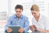 Businessman and woman using digital tablet and cellphone at offi — Stock Photo
