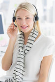 Smiling casual young woman with headset in office — Stock Photo