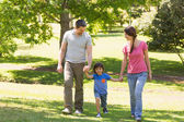 Family of three holding hands and walking at park — Stock Photo