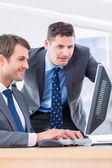 Businessmen using computer at office desk — Stock Photo
