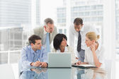 Business people gathered around laptop discussing — Stock Photo