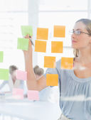 Concentrated artist looking at colorful sticky notes — Stock Photo