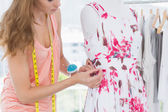 Beautiful female fashion designer working on floral dress — Stock Photo