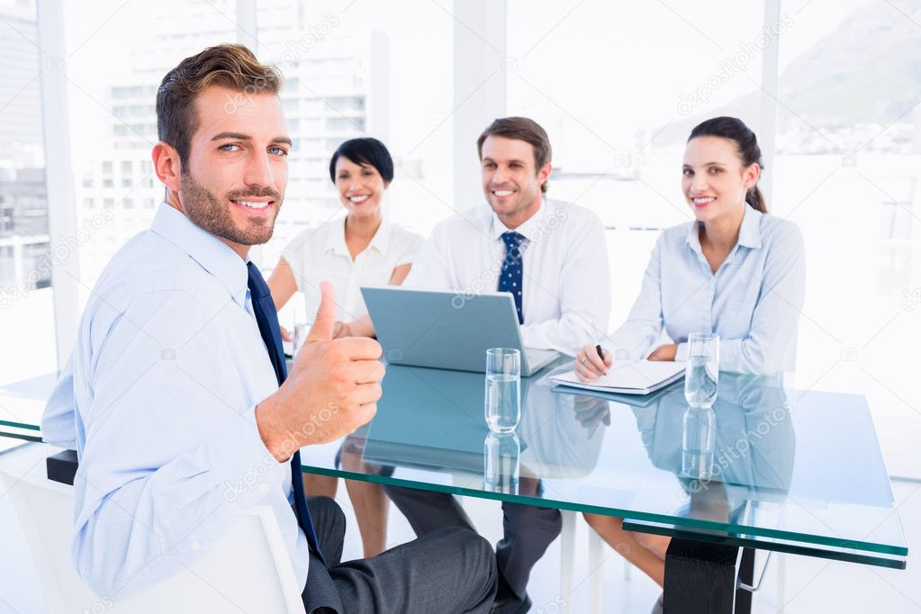 Executive gesturing thumbs up with recruiters during interview ...