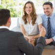 Smiling couple in meeting with a financial adviser — Stock Photo #39190235