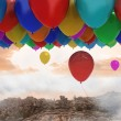 Stock Photo: Many colourful balloons above landscape