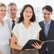Businesswoman holding document smiling at camera with her team — Stock Photo