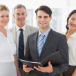 Stock Photo: Businessman holding document smiling at camera with his team