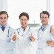 Cheerful doctors gesturing thumbs up at hospital — Stock Photo #39190869