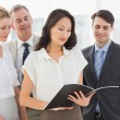 Stock Photo: Businesswoman reading a document with her team