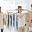 Seller helping shopper choose clothes in store — Stock Photo #39191559