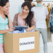 People with clothes donation while using digital tablet — Stock Photo #39191631