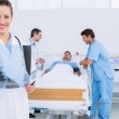 Doctor holding x-ray with surgeons and patient in hospital — Stock Photo