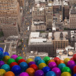 Many colourful balloons above city — Stock Photo #39191859